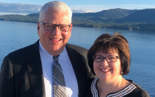 Proforma Affliate Owners Fred and Suzette Albrecht standing side-by-side on a boat with a mountain in the background.